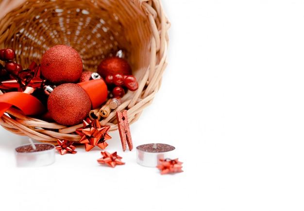 Cesto con decorazioni, palle di natale, fiocco e coriandoli rossi.