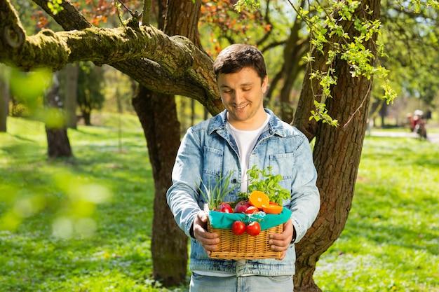 Cesto con frutta e verdura nelle mani di uno sfondo di agricoltore della natura