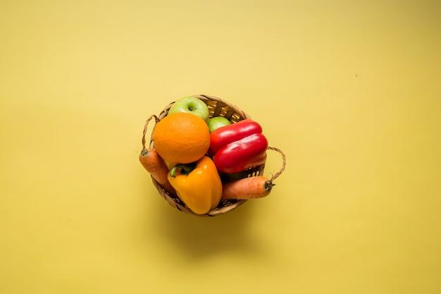 Cesto con frutta e verdura su uno spazio giallo. il cestino contiene peperoni rossi, mele, arance, peperoni gialli e carote. copia spazio