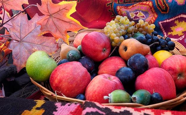 Cesto di frutta al festival del raccolto autunnale. canestro di festival di ringraziamento con foglie di acero