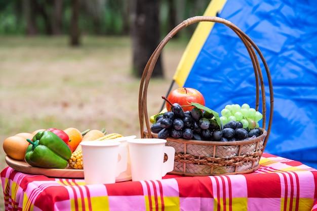 Cesto di frutta, paniera per picnic con cibo sul tavolo e tenda per picnic nel parco.