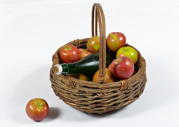 Cesto di mele e bottiglia di sidro