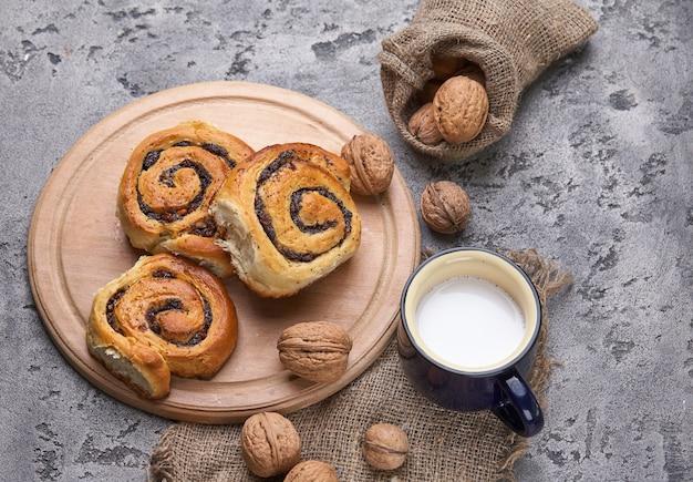 Cesto di panini fatti in casa con marmellata, servito sul vecchio tavolo di legno con noci e tazza di latte