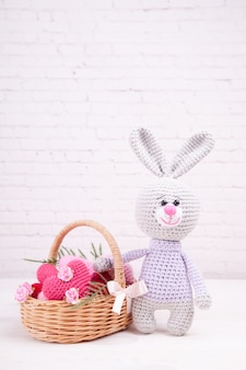 Cesto di vimini con cuori in maglia multicolor. coniglio lavorato a maglia. arredamento festivo. san valentino. giocattolo fatto a mano, a maglia, amigurumi