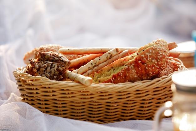 Cesto di vimini con pane. pane, focacce e grissini all'interno del cestino. prodotti da forno freschi sul picnic. messa a fuoco selettiva