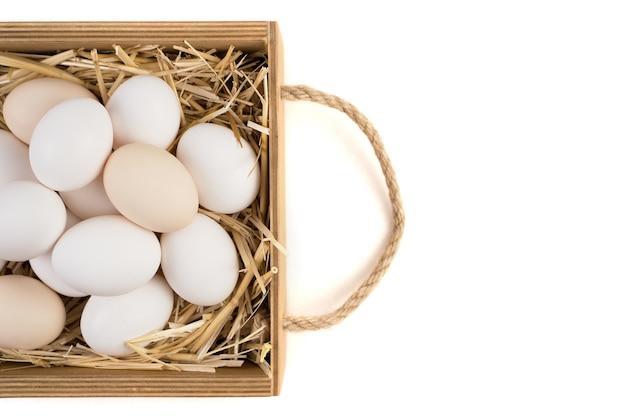 Cesto pieno di uova di gallina che giace sulla vista laterale paglia.