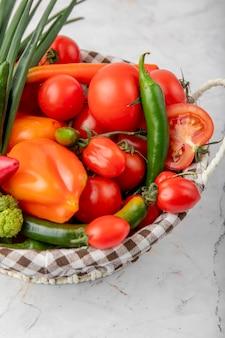 Cesto pieno di verdure come pomodori, peperoni e scalogno sulla superficie bianca