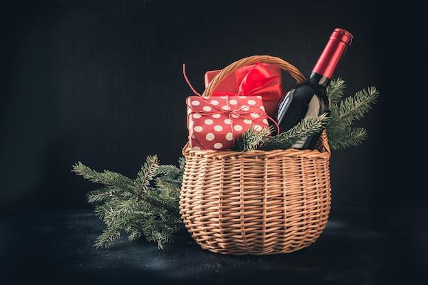 Cesto regalo di natale con vino rosso e regalo sul nero. spazio per i tuoi saluti. carta natale.
