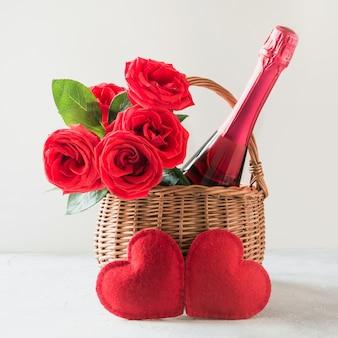 Cesto regalo di san valentino, bouquet di rose, champagne e cuori su bianco.