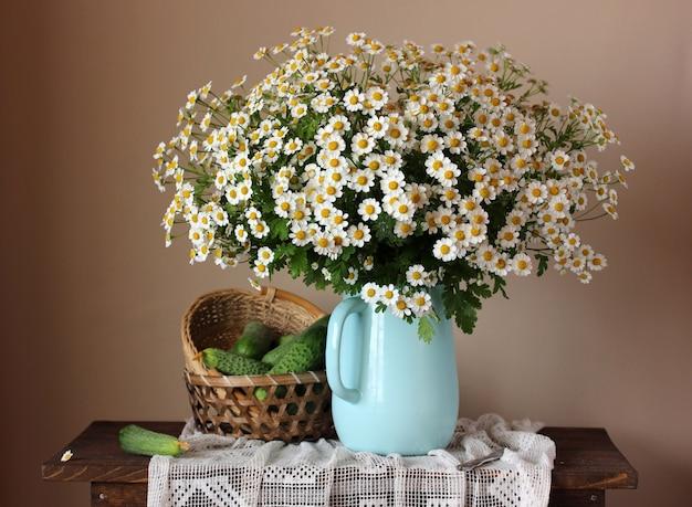 Cetrioli e margherite natura morta con un mazzo di fiori in una brocca e verdure in un cesto sul tavolo.