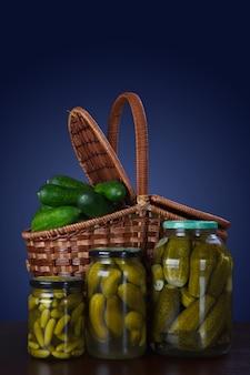 Cetrioli in scatola in barattoli e un cesto di cetrioli freschi.