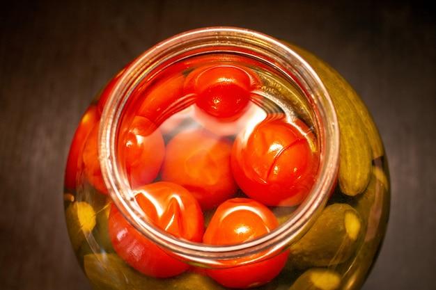 Cetrioli marinati dei pomodori dei sottaceti nel barattolo