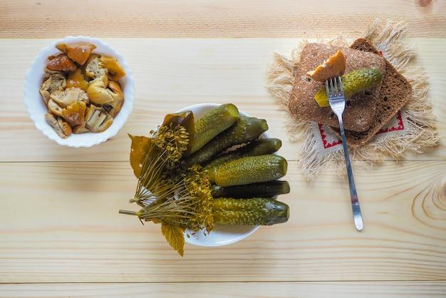 Cetrioli marinati e funghi marinati in una ciotola su un tavolo rustico in legno
