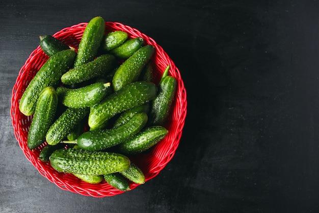 Cetrioli organici freschi nel cestino rosso sul tavolo di legno bianco con verde e rosso e peperoncino, finocchio, sale, grani di pepe neri, aglio, pisello, da vicino, concetto sano, vista dall'alto, piatto