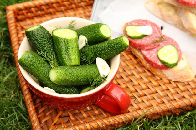 Cetrioli salati freschi fatti in casa nella ciotola sul vassoio di vimini