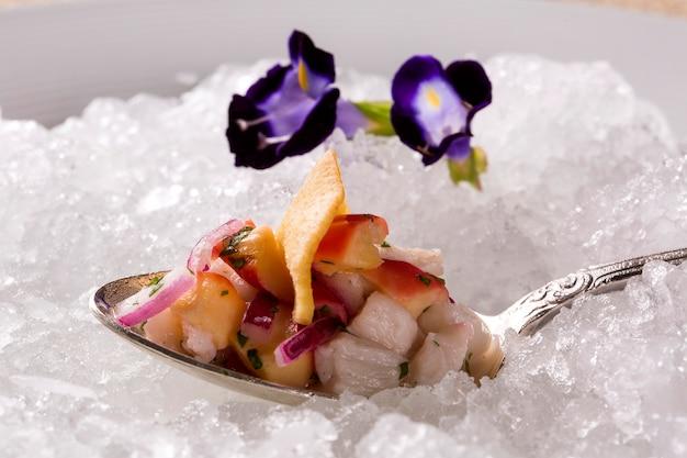 Ceviche servito su vecchi cucchiai nel piatto con ghiaccio. gustoso.