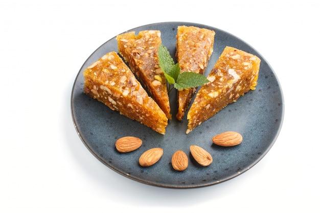 Cezerye turco tradizionale della caramella fatto dal melone caramellato, dalle noci arrostite, dalle nocciole, dai pistacchi in piatto ceramico blu isolato su bianco. vista laterale