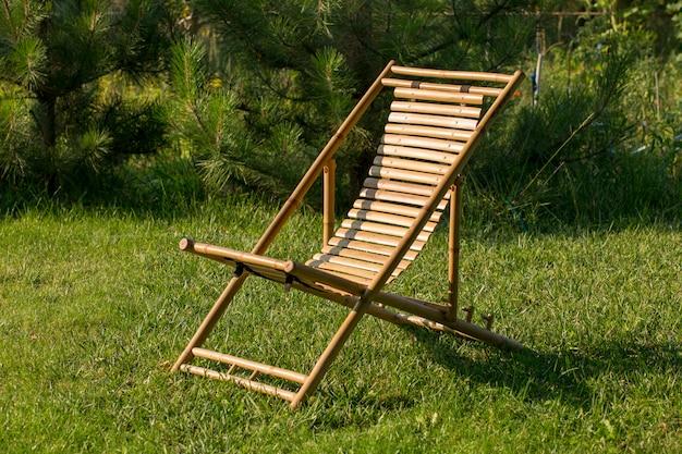 Chaise longue fatta di bambù su un prato verde