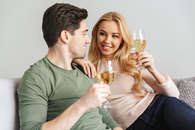 Champagne bevente sorridente del vino bianco dell'alcool delle giovani coppie amorose.