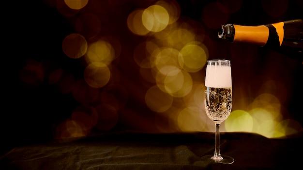 Champagne che versa in vetro con effetto bokeh