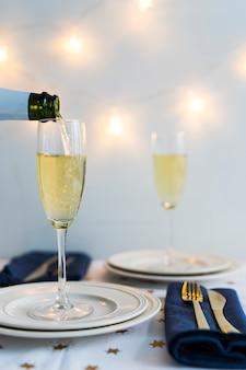 Champagne che versa in vetro sul piatto bianco