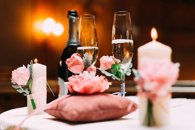 Champagne con due bicchieri, peonie, un piccolo cuscino e candele