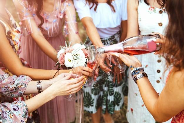 Champagne con gli occhiali nelle mani delle ragazze a addio al nubilato all'aperto.