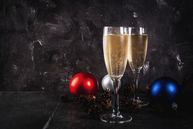 Champagne secco in vetri, palle variopinte di natale, pigne, composizione di natura morta del nuovo anno su fondo di pietra scuro, spazio della copia del fuoco selettivo