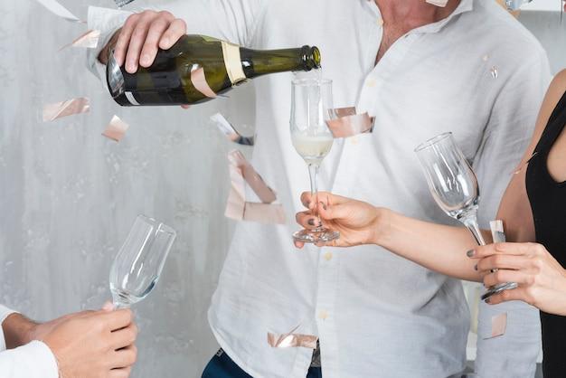 Champagne versando maschio in bicchieri