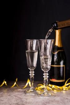 Champagne versando nel bicchiere con stelle filanti alla festa