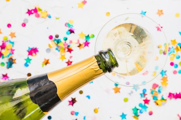 Champagne versando nel bicchiere dalla bottiglia sul tavolo