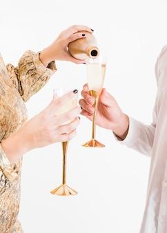 Champagne versato in vetro dalla bottiglia alla festa