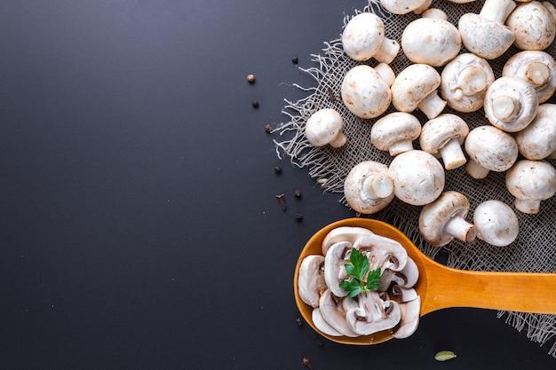 Champignon affettato fresco con prezzemolo in cucchiaio di legno. cucinare deliziosi piatti fatti in casa di funghi bianchi maturi. copia spazio