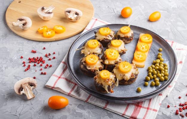 Champignon fritti ripieni con formaggio, kumquat e piselli verdi su grigio