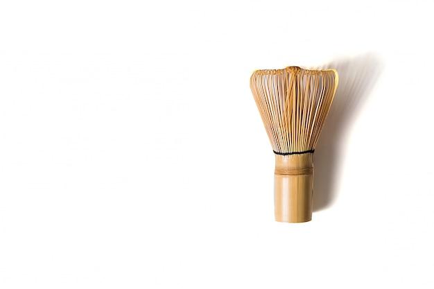 Chasen di bambù per la preparazione del tè di matcha isolato su fondo bianco, disposizione piana.