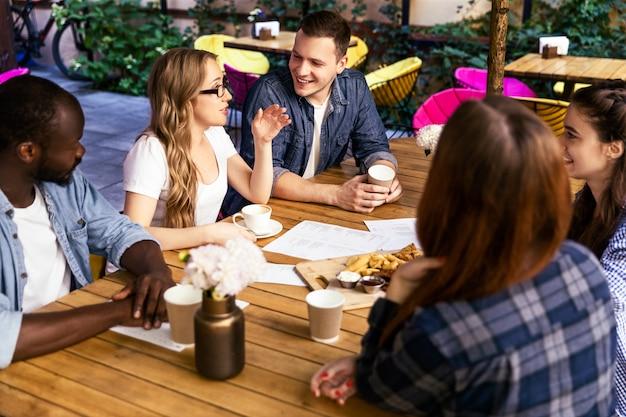 Chat informale con gli amici in un incontro settimanale presso la caffetteria locale in una calda giornata estiva