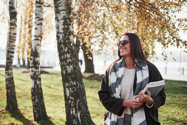 Che bella giornata. il giovane castana sorridente in occhiali da sole sta nel parco vicino agli alberi e tiene il blocco note