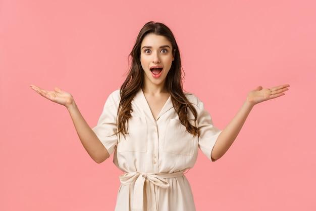 Che piacevole sorpresa. fascino felice divertito, splendida femmina bruna in abito carino, mani aperte accoglienti lateralmente e sorridente stupito, saluto amico, in piedi muro rosa