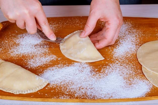 Chebureki. cucinare a casa chebureki non tostato con farina su una tavola di legno.