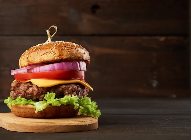Cheeseburger con pomodori, cipolle, cotoletta barbecue e panino al sesamo su un vecchio tagliere di legno, sfondo marrone. fast food, copia spazio