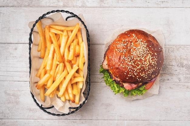Cheeseburger e patatine fritte in un cestino di metallo.