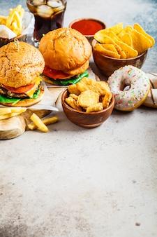 Cheeseburger, patatine fritte, nachos, ciambelle, soda e pepite