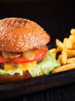 Cheeseburger saporito del primo piano con le patate fritte