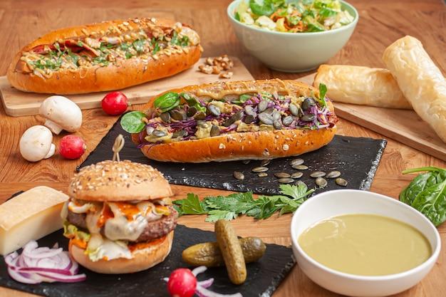 Cheeseburger, selezione di hot dog, insalata e zuppa
