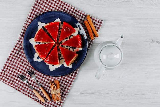 Cheesecake a fette in un piatto e un panno da picnic con una teiera, due forchette e bastoncini di cannella distesi su uno sfondo grigio chiaro