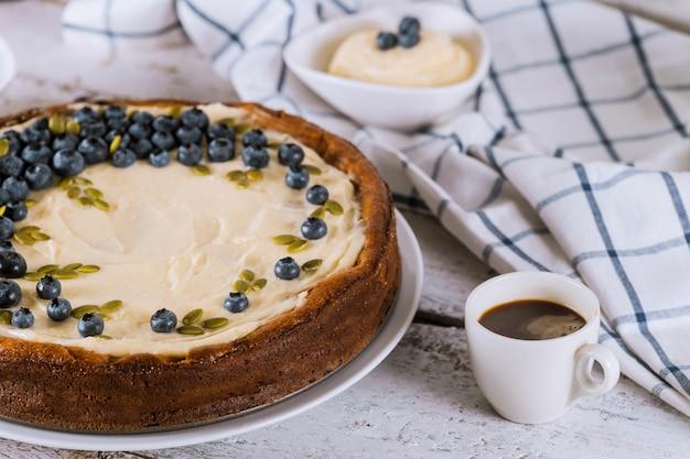 Cheesecake ai mirtilli, tazza di caffè e budino
