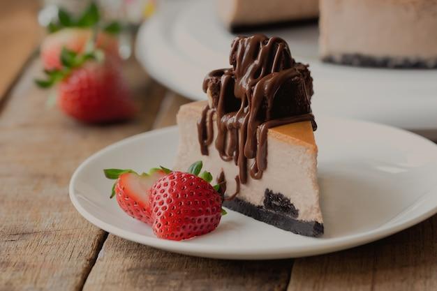 Cheesecake al cioccolato fatto in casa condita con brownie e salsa al cioccolato fondente e fragola