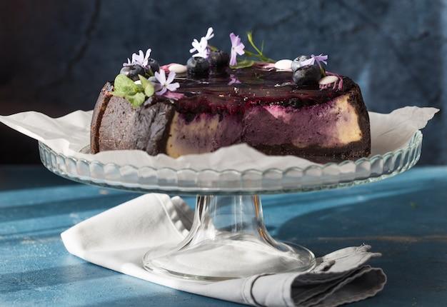 Cheesecake al gusto di mirtillo roteato con salsa di mirtilli su una briciola di biscotti