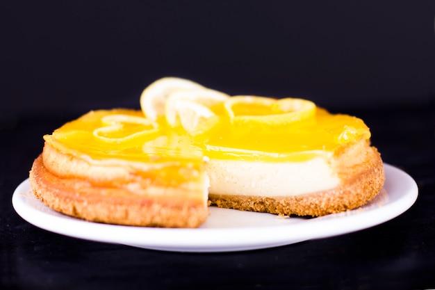 Cheesecake al limone su fondo nero decorato con la scorza di limone si chiuda