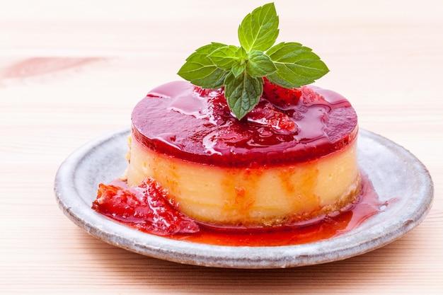 Cheesecake alla fragola con menta fresca su fondo di legno.